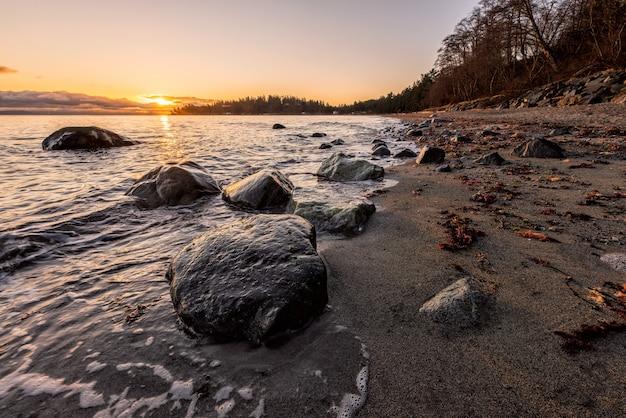 일몰시 해변에 회색 바위