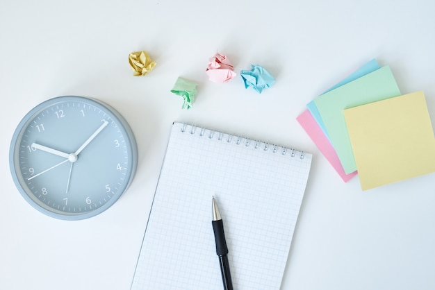 Gray round alarm clock colorful sticky notes and notebook on white