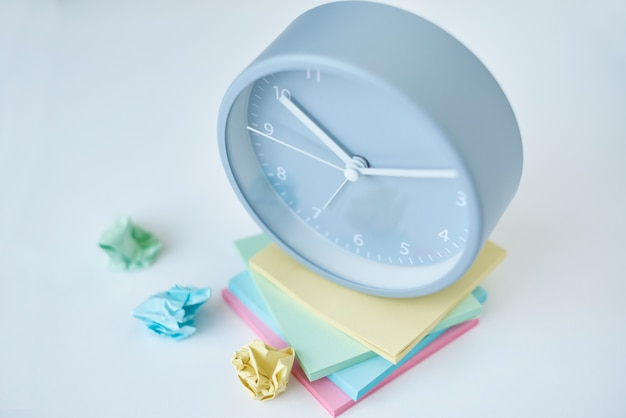 Gray round alarm clock and colorful sticky notes