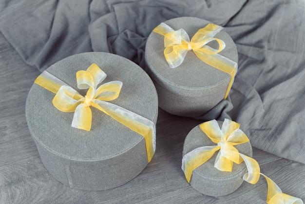 Серые круглые подарочные коробки с желтой лентой