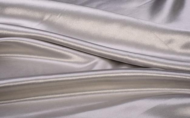 Серая предпосылка ткани яркого блеска сатинировки роскошная с космосом экземпляра, предпосылками; текстурированный; текстиль; шелк