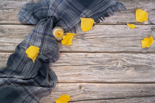 Gray scarf and dry leaves of yellow color on wood surface