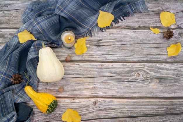 Серый шарф, тыквы и сухие листья желтого цвета на деревянной поверхности