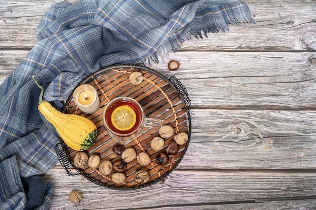 Серый шарф, чай и осенний декор на деревянной поверхности