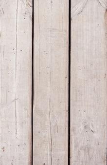灰色の傷の古い木製の背景。通りの古い木。垂直の木製の背景、碑文の場所。