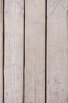 灰色の傷の古い木製の背景。通りの古い木。垂直の木製の背景。