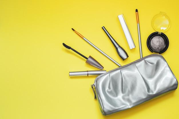 노란색 배경에 회색 빛나는 화장품 가방. 텍스트에 대 한 장소입니다. 2021년 트렌드 컬러.