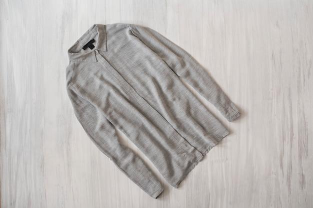 Серая рубашка на деревянных фоне. модная концепция