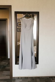 A gray silver elegant dress hangs in the room on the mirror. dress for an adult bridesmaid
