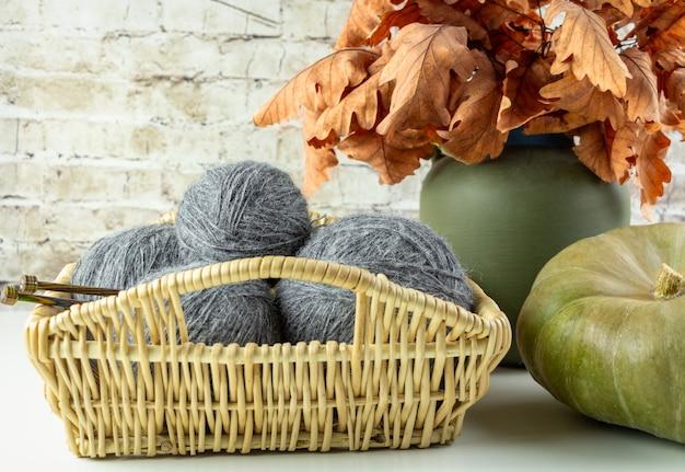 Серые мотки пряжи лежат в плетеной корзине на фоне букета из осенних листьев и тыкв.