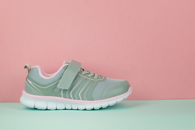 Gray sneaker on the right foot on a blue and pink background.