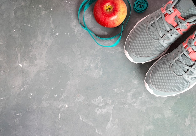 Gray sneakers, apple on gray background. fitness background