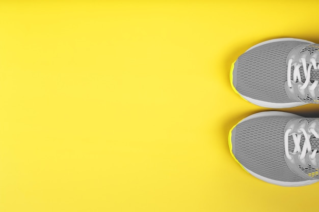Gray sneakers isolated on yellow