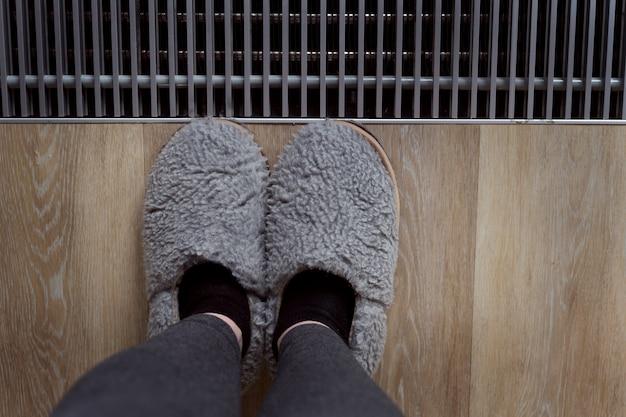 Серые кроссовки. фотография ног в серых тапочках у окна. домашняя атмосфера