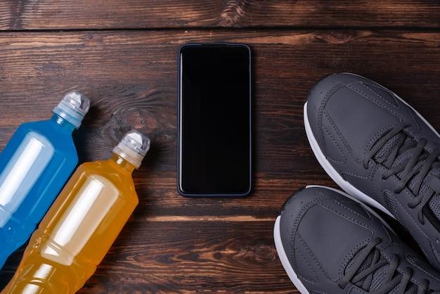 회색 운동화, 스마트폰, 그리고 짙은 나무 배경에 있는 두 병의 등장성 음료, 모형, 스포츠 훈련 개념이 닫힙니다.