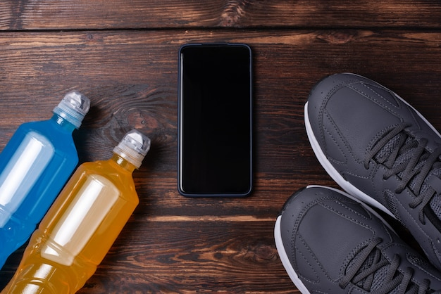 Gray sneakers, smartphone and two bottles of isotonic drink on a dark wooden background, mockup, sports training concept, close up.