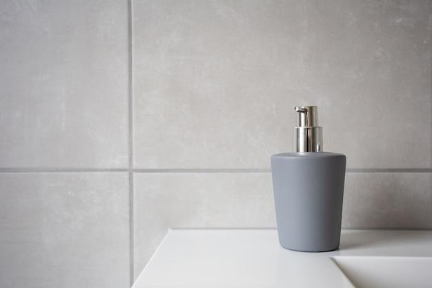液体石鹸用グレーソープディスペンサー、天然石タイル張りのバスルーム