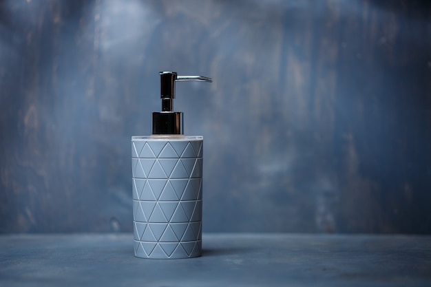 Gray soap dispenser with a metal cap on a gray table