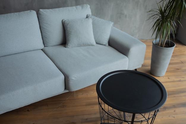 灰色のソファの植木鉢と黒のデザイナーテーブル