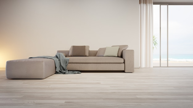 Gray sofa near blank wall on empty wooden floor of large living room in modern house or luxury villa