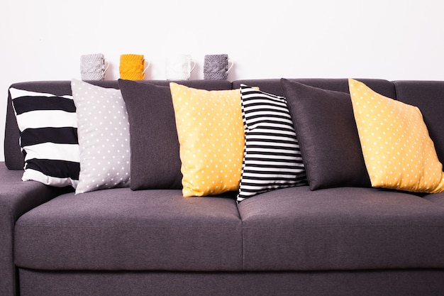 Серый диван с множеством разноцветных подушек