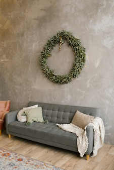 Gray sofa with pillows, over the sofa on the wall hangs a christmas wreath. scandinavian style in the living room