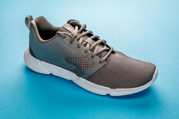 Gray sports sneakers isolated on a blue . sport shoes