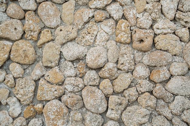 灰色の石の壁の背景、丸みを帯びたベージュの石