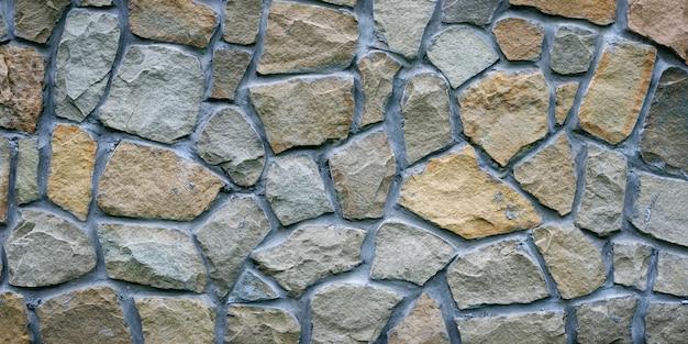 회색 돌 담입니다. 회색 화강암의 질감입니다. 바닥의 고르지 못한 바위 표면, 외관 건물의 장식 타일. 넓은 파노라마.