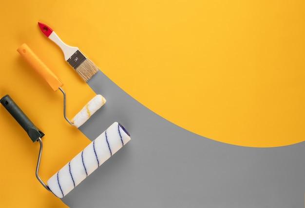 롤러에서 페인트의 회색 줄무늬와 노란색 배경에 brushe. 홈 리노베이션 개념.