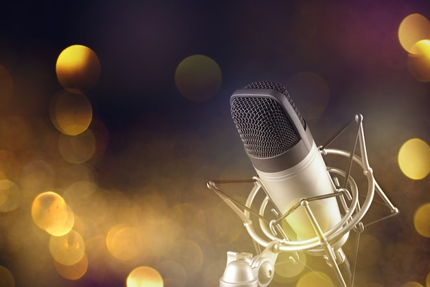 Gray studio condenser microphone in shock mount on blur festive holiday lights surface. copy space