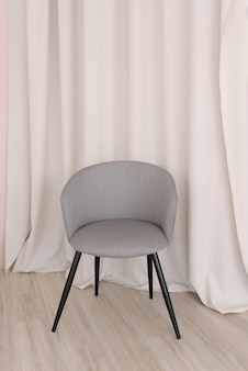 Gray stylish chair against the background of the curtains in the living room