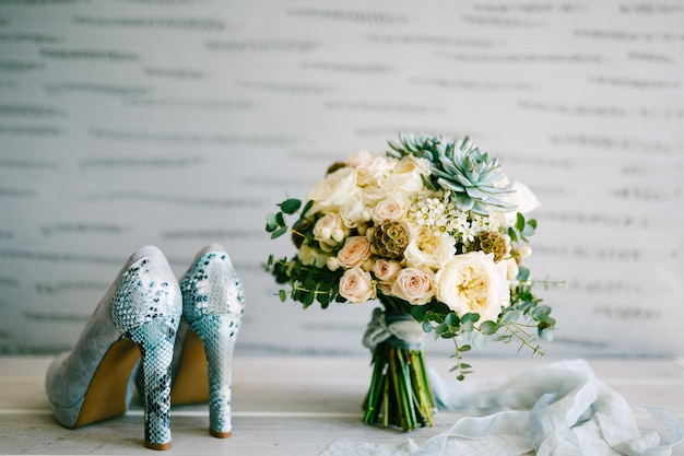 Gray suede shoes with snakeskin heels next to a bridal bouquet with silk ribbons