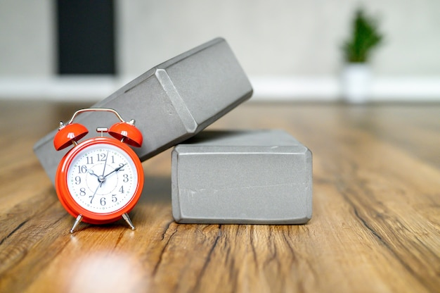木の床に赤い目覚まし時計が付いているスポーツ用の灰色のサポート キューブ