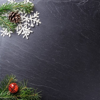 Gray surface with christmas ornamental pine branches and a snowflake with copy space