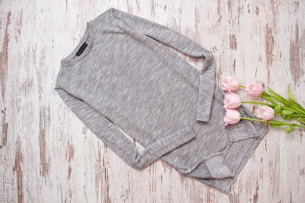 木製の背景に灰色のセーターとピンクのチューリップ