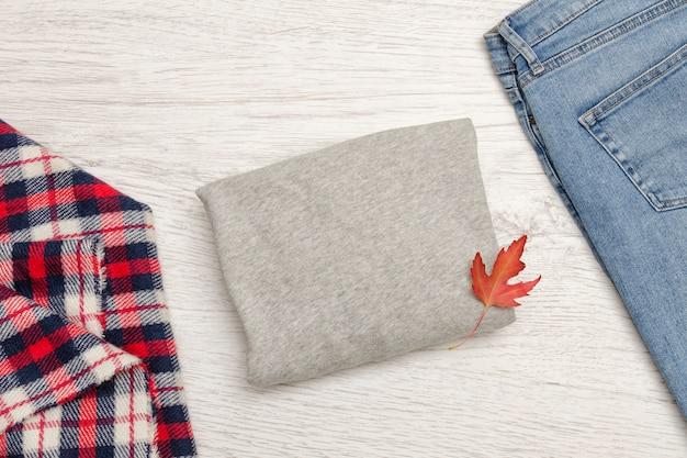 Gray sweater, blue jeans, scarf and autumn leaf