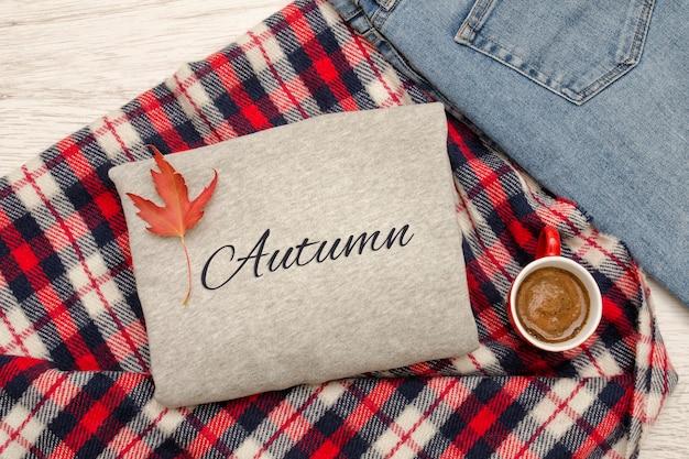 グレーのセーター、ジーンズ、チェック柄、コーヒー。紅葉。ファッショナブルなコンセプト