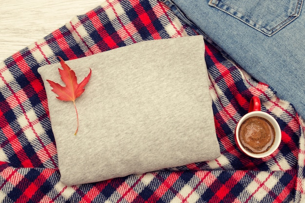 Gray sweater, jeans,  plaid and coffee mug. autumn leaves. fashionable