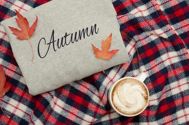 グレーのセーター、チェック柄、コーヒーマグ。紅葉。ファッショナブルなコンセプト