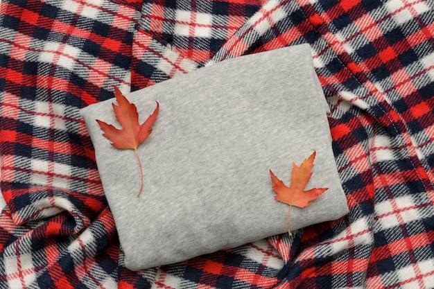 灰色のセーター、格子縞、コーヒーマグ、紅葉。ファッショナブルなコンセプト