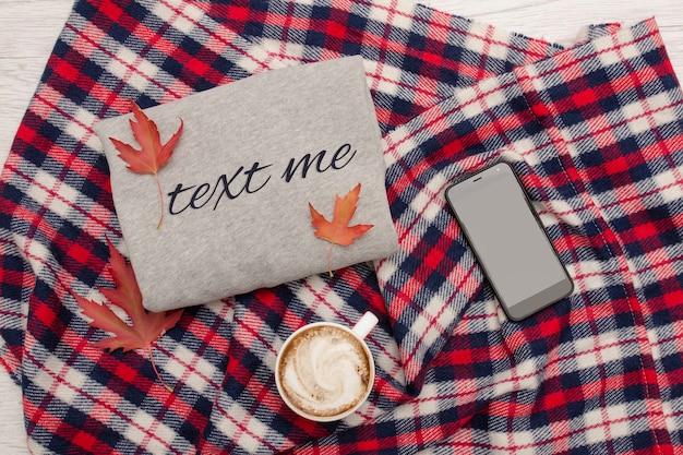 灰色のセーター、格子縞、一杯のコーヒーとスマートフォン。紅葉。ファッショナブルなコンセプト