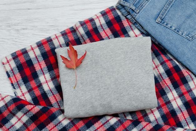 Серый свитер, плед, джинсы и осенние листья