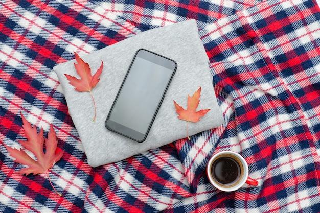 灰色のセーター、スマートフォン、格子縞、コーヒーのマグカップ。ファッショナブルなコンセプト