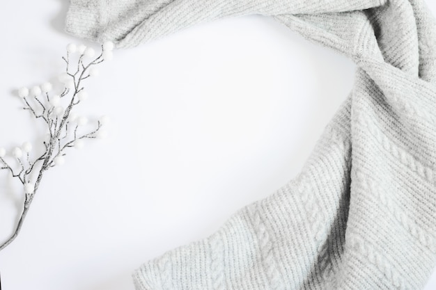 Gray sweater and white branch on a white background