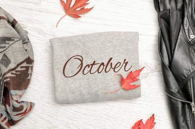 10月の碑文、黒いジャケット、スカーフ、紅葉のある灰色のセーター。ファッショナブルなコンセプト
