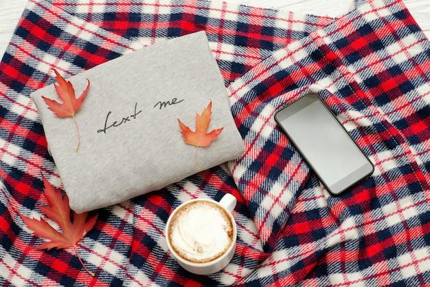 碑文、格子縞、スマートフォン、カプチーノマグカップ、紅葉のグレーのセーター。ファッショナブルなコンセプト