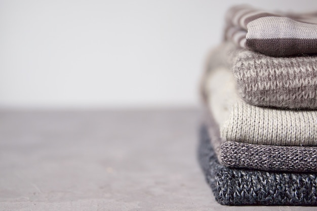 Gray sweaters stacked on a gray background copy space