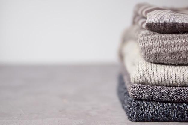 Серые свитера сложены на сером фоне копией пространства