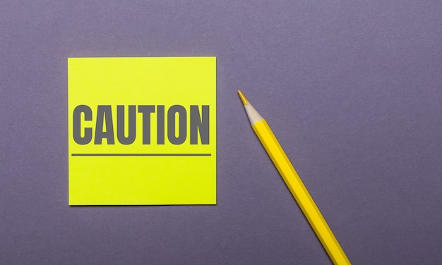 On a gray table, a bright yellow pencil and a yellow sticker with the word caution